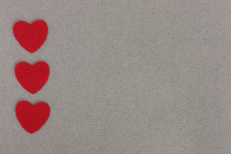 red felt hearts on grey paper background with space for inscription