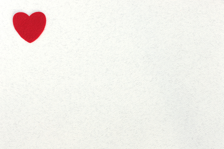 red felt hearts on white paper background with space for text without people abstract
