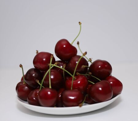 A bunch of ripe cherries with peduncles lies in a white plate. Large collection of fresh red cherries. Ripe cherries background. Close up.