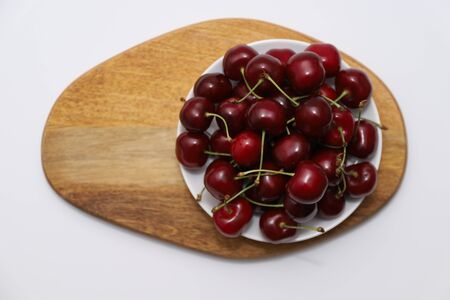 A bunch of ripe cherries with peduncles lies on a wooden stand. Large collection of fresh red cherries. Ripe cherries background. Close up.