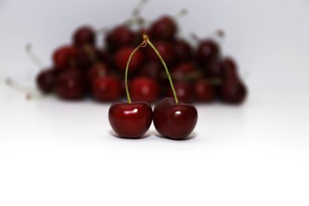 A bunch of ripe cherries with peduncles lies on a white background. Large collection of fresh red cherries. Ripe cherries background. Close up. isolate Reklamní fotografie