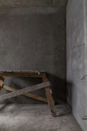 Home improvement. A dirty construction staircase in an empty room with gray concrete walls background 版權商用圖片