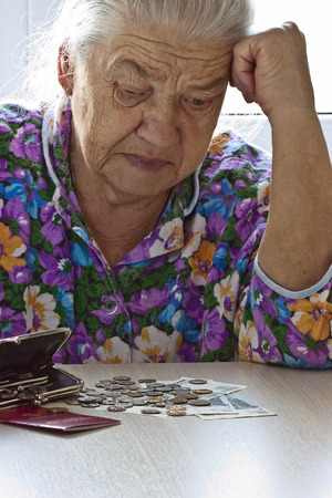 elderly  woman counting money on table