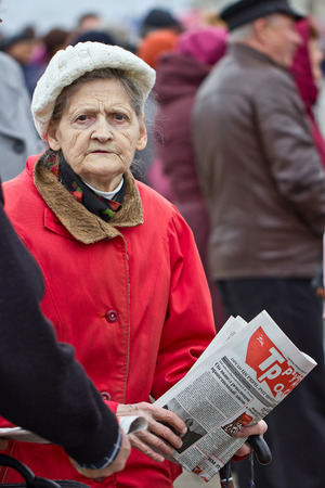 demonstrators: Mature woman with a newspaper in his hands Editorial
