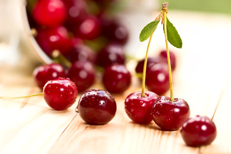 Cherries on wooden table with water drops macro photo