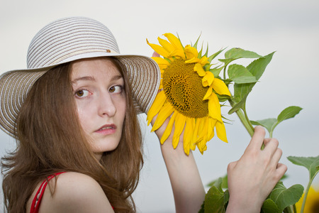 Beautiful young woman with sunflower photo