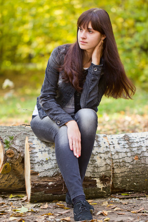 felled: Young girl sitting on a felled tree