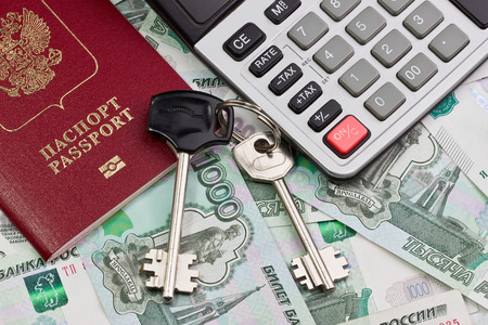 Passport, keys and calculator against the background of Russian money photo