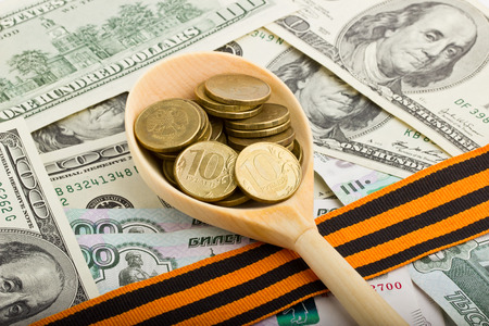 georges: Spoon with coins on a background of money  with St. Georges ribbon