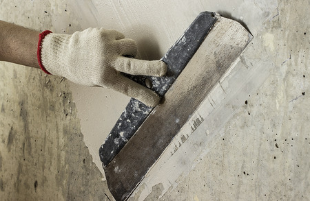 putty knives: Process putty concrete wall with a metal spatula Stock Photo