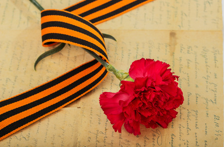 heroism: Carnations, St. George ribbon and an old letter. Symbol of heroism