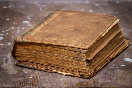 ancient book: Ancient book in a grunge style on old wooden table Stock Photo