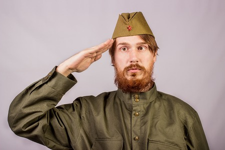 Young bearded man dressed in historical soviet  uniform on gray background Stock Photo
