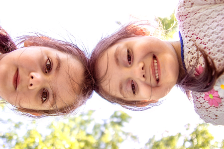 bending down: Low angle  portrait of two young girls  bending down against sky Stock Photo