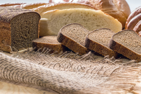 long loaf: Rye bread and white long loaf on an old wooden table Stock Photo