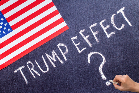 Trump Effect on the chalk board and US flag. Election concept 写真素材