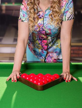 Femme debout près de la table de billard