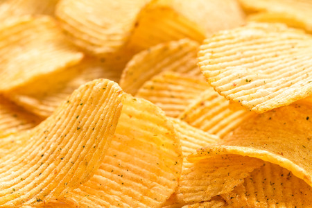 Yellow salted potato chips as background, closeup. Chips texture studio photo Stock Photo