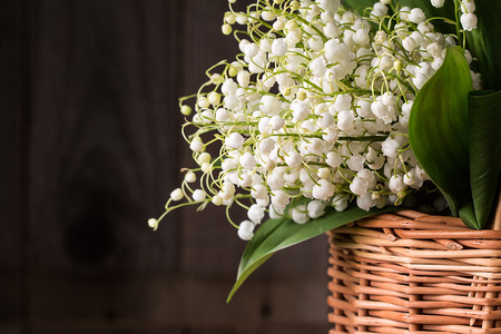bouquet of lilies of the valley in a wicker basket on a wooden background Stock Photo