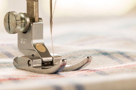 Closeup of sewing machine and fabric. Empty space for text