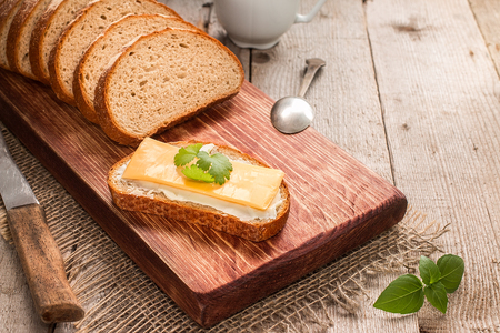 Butter and bread for breakfast, with parsley over rustic wooden background