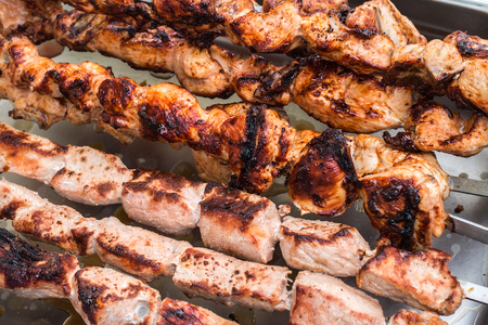 Shashlik roasting on hot grill, one piece scorched