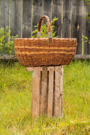 Big old weathered empty wicker laundry basket on wooden log on green grass country garden meadow