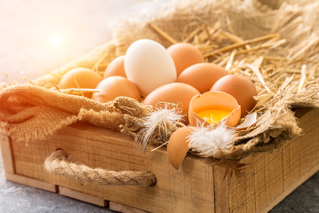 bunch of fresh brown eggs and some straw in a wooden crate  Stock Photo