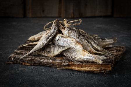 Dried fish lies on dark stone  surface. Food background