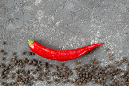Fresh Chili pepper and peppercorns over gray stone background. Raw organic spices. Healthy lifestyle.  Top view with copy space.  culinary background Imagens