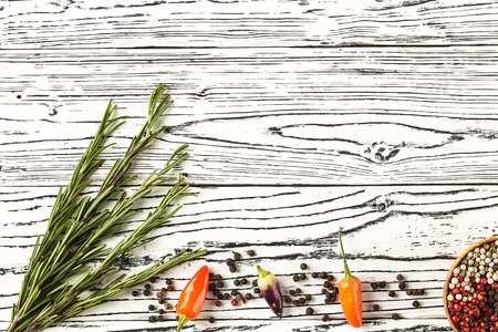 background rosemary, chili pepper on a wooden table. Herb and spice ingredients on  wooden white background