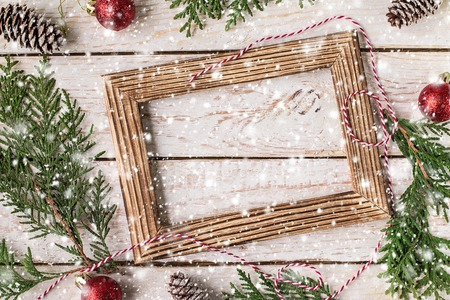 Christmas decoration on the white wooden background. Christmas interior with photo frame, decorative branches, presents on wooden table. New Year winter composition. Top View. Space for text
