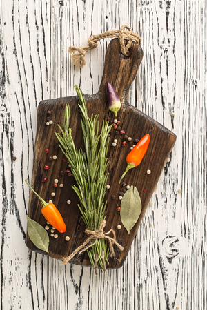 Cutting Board, rosemary and spices. background rosemary, chili pepper on a wooden table.  Herb and spice ingredients on  wooden white background