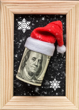 Dollars on wooden photo frame.  Winter holidays concept.