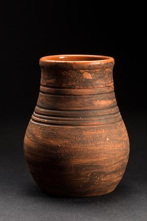 Old Brown ceramic pot on dark  background. Old kitchen utensils, selective focus Banco de Imagens