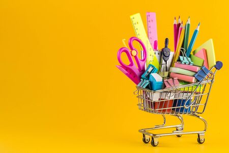 Shopping cart with School stationery on yellow background. Back to school Education concept.Colorful school supplies in shopping cart