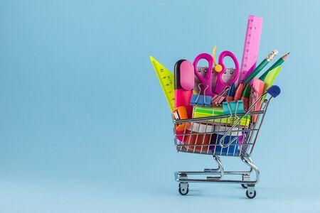 Carro de compras con diferentes artículos de papelería sobre fondo azul. Foto de archivo