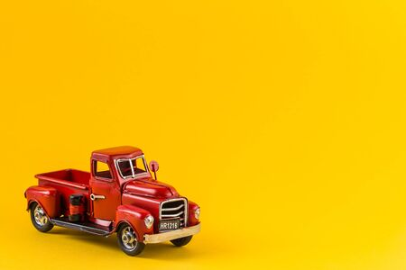 Red toy truck on bright yellow background. Metal model of an old truck