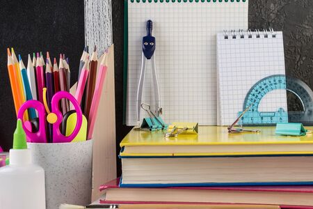 School stationery on a table in front of blackboard. Colorful stationary in concept creative school work. Back to school concept. Reklamní fotografie