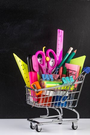 Shopping cart stocked with school supplies and a blackboard in the background. Back to school Education concept.Colorful school supplies in shopping cart