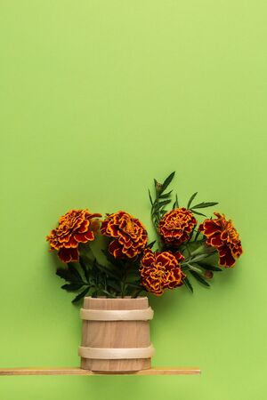 Bouquet flowers marigold in a wooden vase on a green pastel paper background. Flat lay, top view floral background. Minimalism fashion style