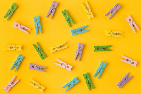 Little colorful clothes pins on yellow background. laundry clips disorganized on blue background, with copy space. Trendy minimal style. Top view, Flat lay.