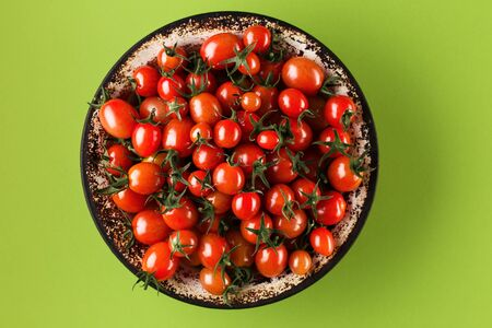Flat lay with red tomatoes on green background. tomatoes in a metal plate on bright green paper background. Trendy minimal style. Top view, Flat lay.