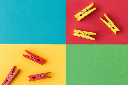 Little wooden clothespins on colorful paper background. Trendy minimal style. Top view, Flat lay. Reklamní fotografie