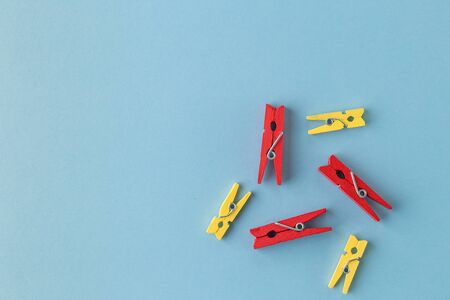 Little colorful clothes pins on a blue background. laundry clips disorganized on blue background, with copy space. Trendy minimal style. Top view, Flat lay.