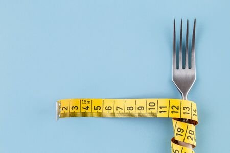 Fork with a measuring tape, diet or healthy eating concept. Proper nutrition. Medical starvation. Diet for weight loss concept. Free space for text. Reklamní fotografie