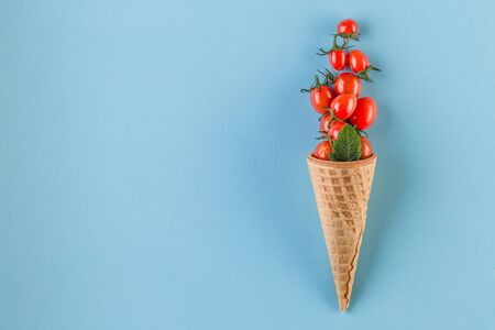 Healthy fresh tomatoes in waffle cones on blue paper background. Vegan and vegetarian diet concept. Top view. Trendy minimal style. Flat lay composition Reklamní fotografie