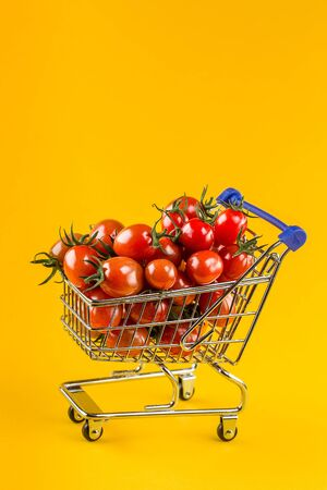 juicy tomatoes in shopping cart on yellow paper background. Copy space.Trendy minimal style