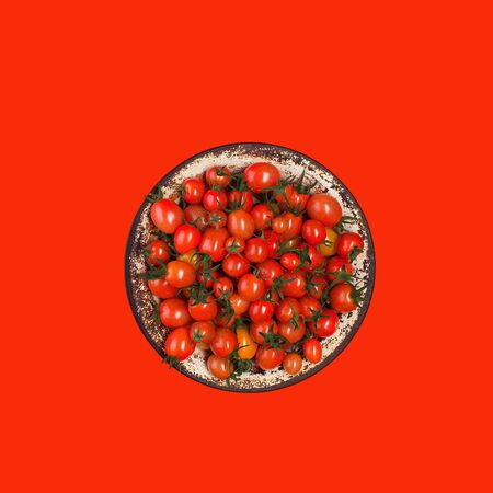 Flat lay with red tomatoes on red background. tomatoes in a metal plate on bright red paper background. Trendy minimal style. Top view, Flat lay.