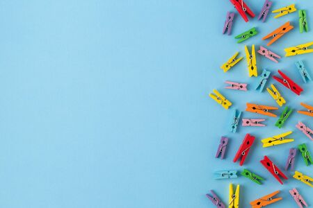Little wooden clothespins  on  bright blue paper background. Colourful clothespins with copy space. Trendy minimal style. Top view, Flat lay Reklamní fotografie